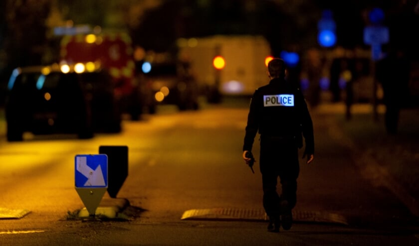 <p>Een Franse agent patrouilleert in de Parijse wijk waar vrijdagavond een leraar vermoord werd.</p>  (beeld afp / Abdulmonam Eassa)