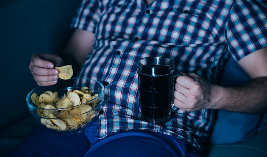 overweight man watching tv with junk food and beer. overeating, sedentary lifestyle, bad habits, food addiction, eating disorders  (beeld istock)