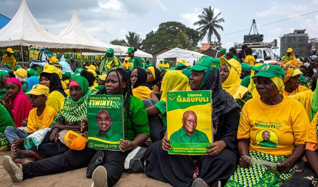 <p>Aanhangers van regeringspartij Chama Cha Mapindunzi (CCM) tonen tijdens een campagnebijeenkomst borden van de kandidaat voor Zanzibar Hussein Mwinyi (links) en de presidentskandidaat voor Tanzania John Magufuli.</p>  (beeld afp / Patrick Meinhardt)