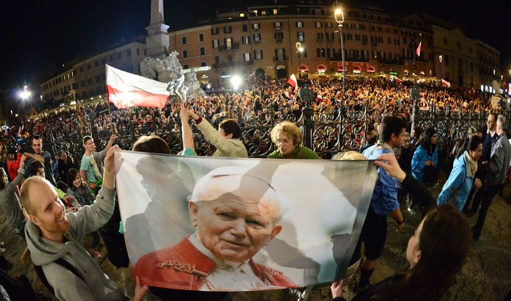 Een menigte in het centrum van Rome viert de heiligverklaring van paus Johannes Paulus II, tegelijk met paus Johannes XXIII, in 2014.   (beeld afp / Giuseppe Cacace)