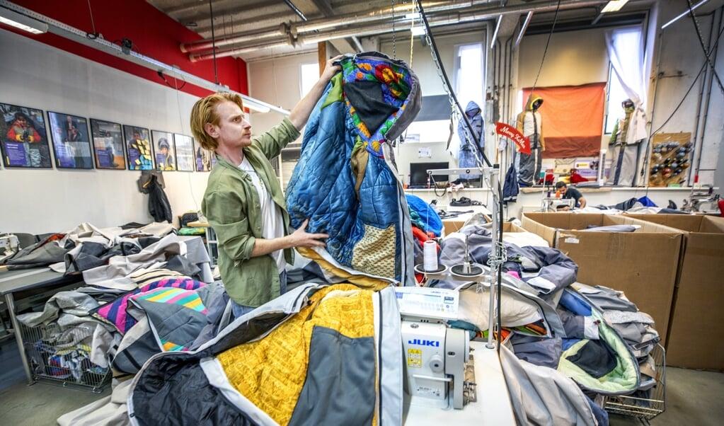 <p>Bas Timmer met tweedehandsslaapzakken waarvan in zijn atelier sheltersuits voor daklozen worden gemaakt.</p>  (beeld Raymond Rutting )