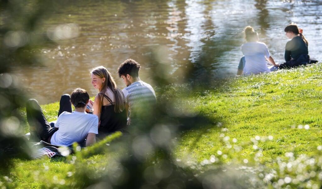 <p>Mensen genieten van de zon. Een tekort aan vitamine D, waarvan zonlicht de aanmaak bevordert, zou nadelig zijn bij een coronabesmetting.</p>  (beeld anp / Piroschka van de Wouw)