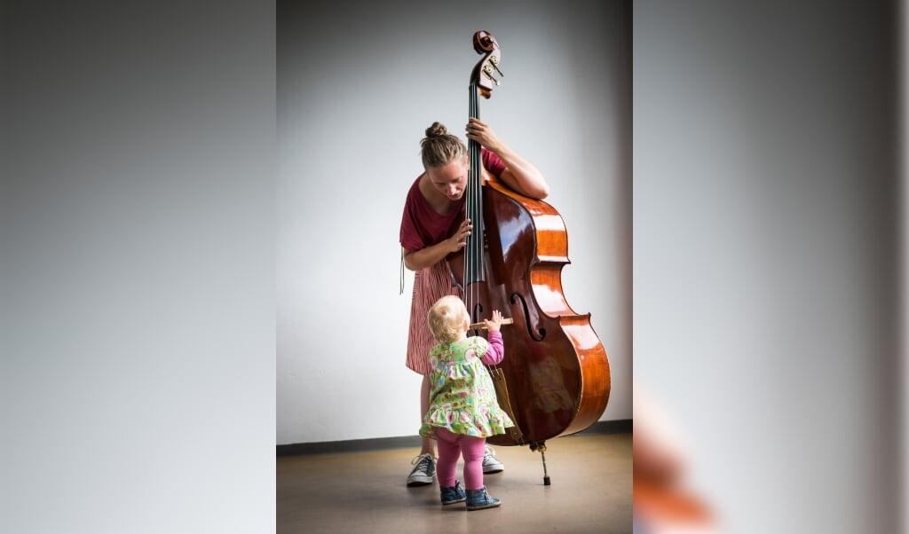 <p>Dorie ten Hove met haar contrabas tijdens een muziekles.</p>  (beeld Mariska de Groot)