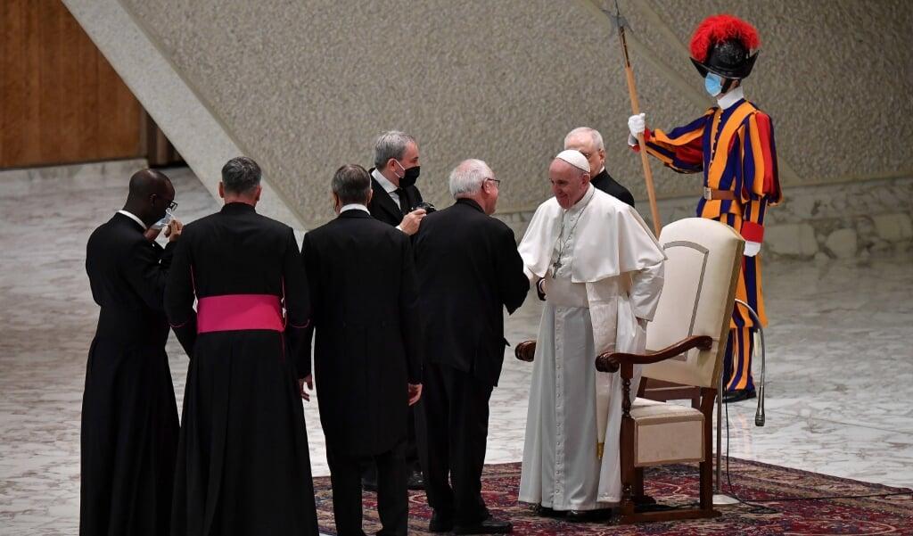 <p>Terwijl deelnemers in de grote aula hun maskers verplicht dragen volgens de Vaticaanse regels, draagt paus Franciscus het masker niet. Na afloop van de algemene audiëntie op woensdag groette hij verschillende mensen die hij ongemaskerd toesprak. De beide geestelijken links op de foto doen hun masker af alvorens de paus de hand te geven.</p>  (beeld Epa/alessandro di meo)