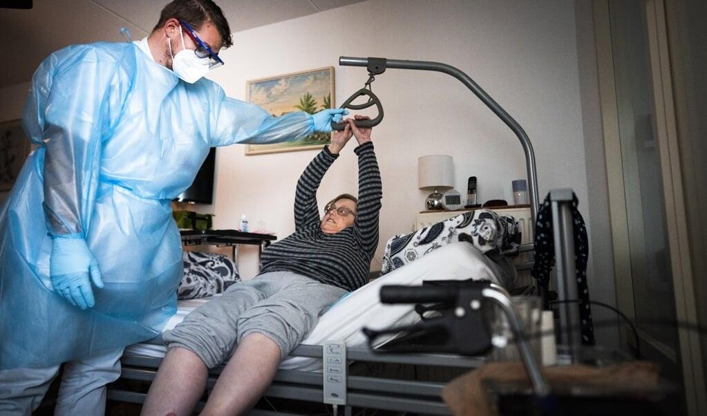 <p>Verpleegkundige Arjo Verheijen helpt mevrouw Van de Poll in haar woning in Rotterdam. </p>  (beeld Freek van den Bergh)