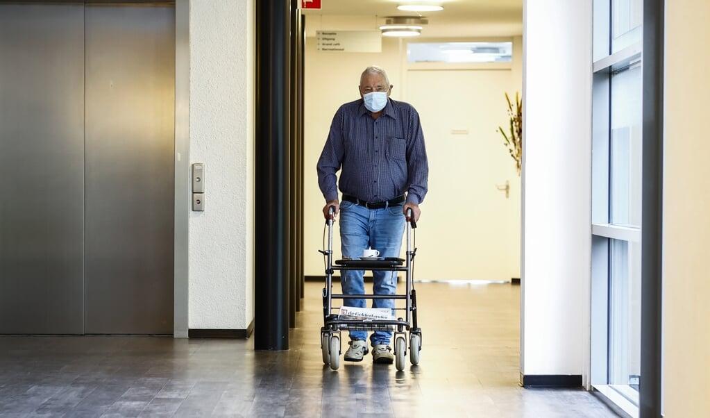 Een bezoeker met mondkapje bij verpleeghuis De Bleijke in Hengelo.  (beeld anp / Vincent Jannink)