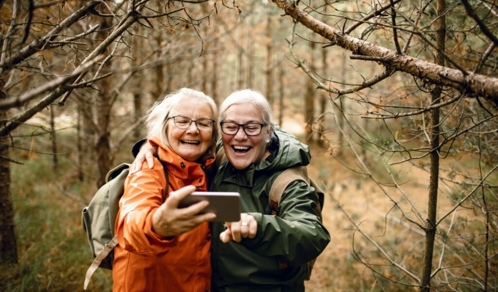 Close up of two female seniors taking a selfie while hiking in the forest  (beeld istock)