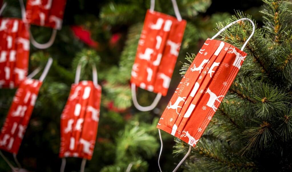 Mondkapjes in een kerstboom. Tijdens de feestdagen spelen veel ondernemers in op het verkopen van kerstartikelen die inhaken op het coronavirus.  (beeld anp / Xtra lex van Lieshout)