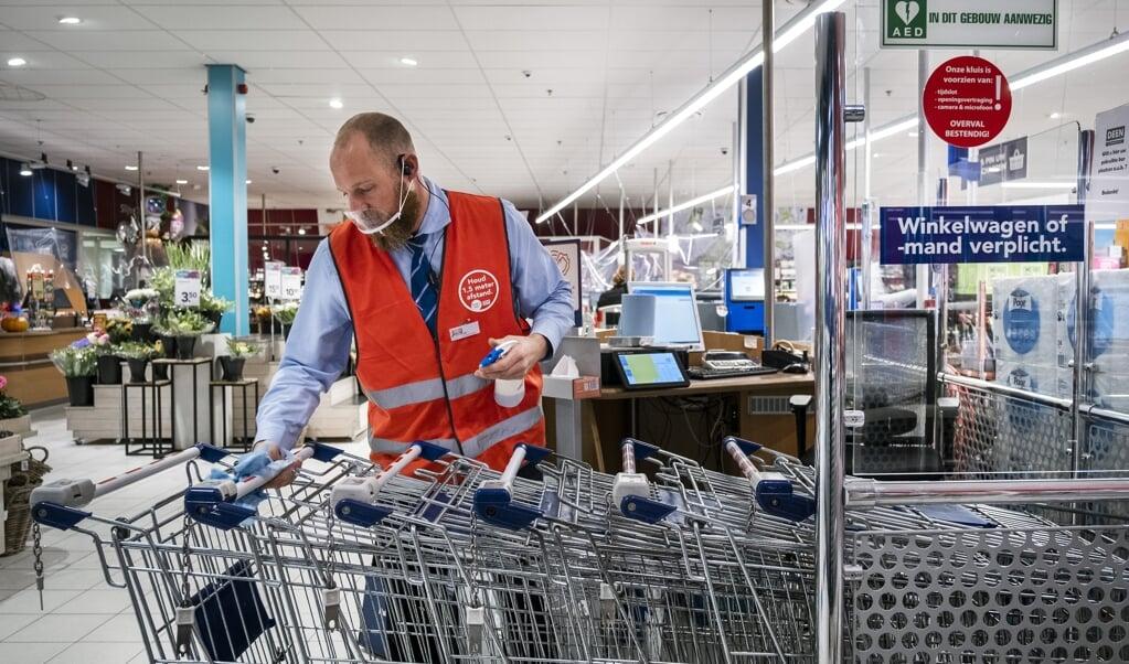 Desinfectie van winkelwagentjes.  (beeld anp / Ramon van Flymen)