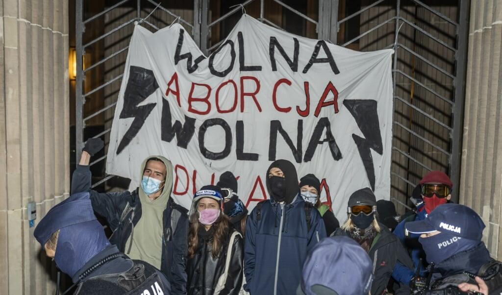 De politie greep maandag in bij een protest van pro-abortusbetogers voor het ministerie van Onderwijs in Warschau.  (beeld afp / Wojtek Radwanski)