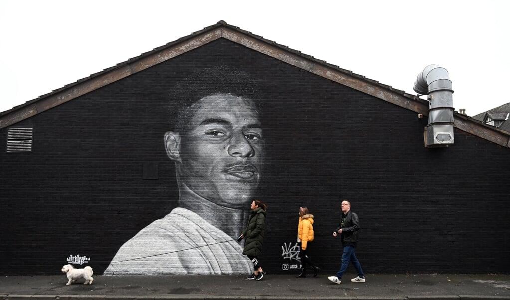 Marcus Rashford in graffiti in de wijk Withington in Manchester.  (beeld afp / Paul Ellis)