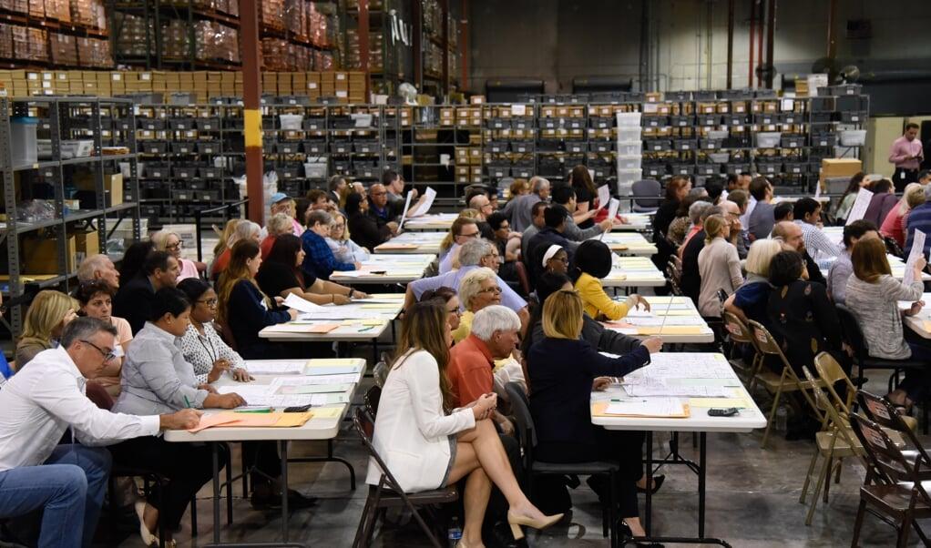 Een van de vele hertellingen van de stemmen in de VS, hier in Palm Beach County in Florida in 2018, waar vrijwilligers toezien op een correcte gang van zaken.  (beeld afp / Michele Eve Sandberg)