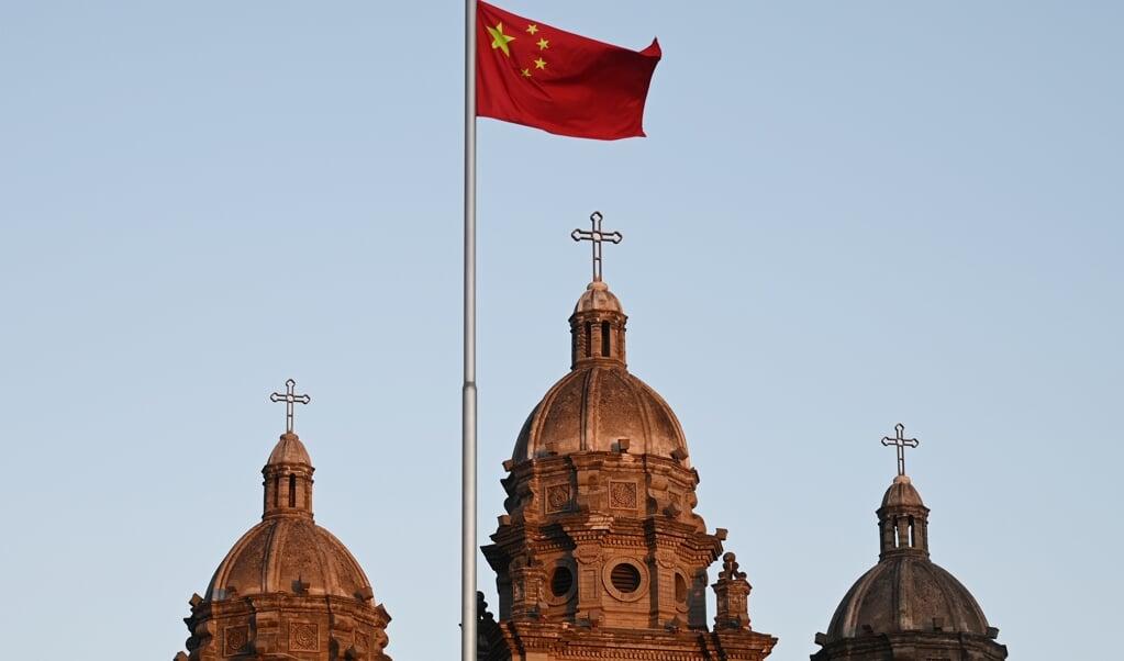 De Chinese vlag voor de Sint-Jozefkerk in Peking, wapperend op 22 oktober 2022, de dag waarop China en het Vaticaan hun akkoord over bisschopswijdingen verlengden.  (beeld Greg Baker / afp)