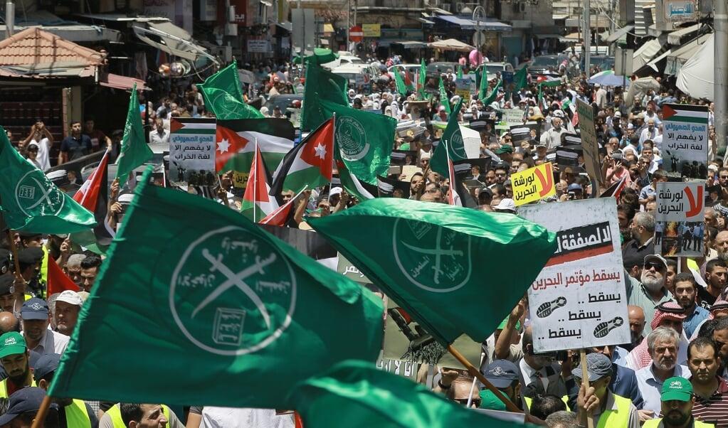 De groene vlaggen van de Moslimbroederschap in 2019 bij een demonstratie in de Jordaanse hoofdstad Amman. De broederschap heeft zich in de loop van de jaren sterk ontwikkeld in democratische richting. Al blijven er rode lijnen: mogelijkheden voor vrouwen, het recht openlijk de islam te verlaten en het beledigen van Mohammed.  (beeld Khalil Mazraawi / afp)