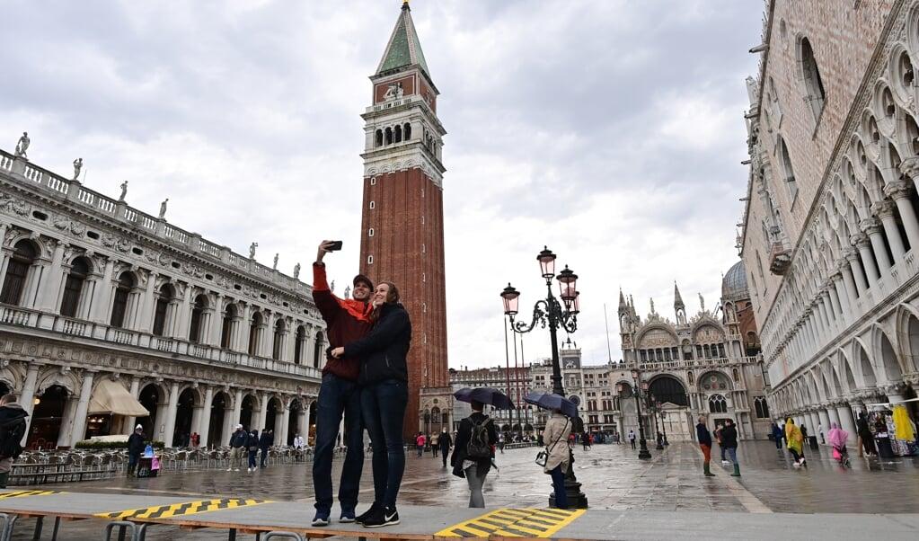 Toeristen nemen een selfie op het San Marcoplein in Venetië.   (beeld Miguel Medina / afp)