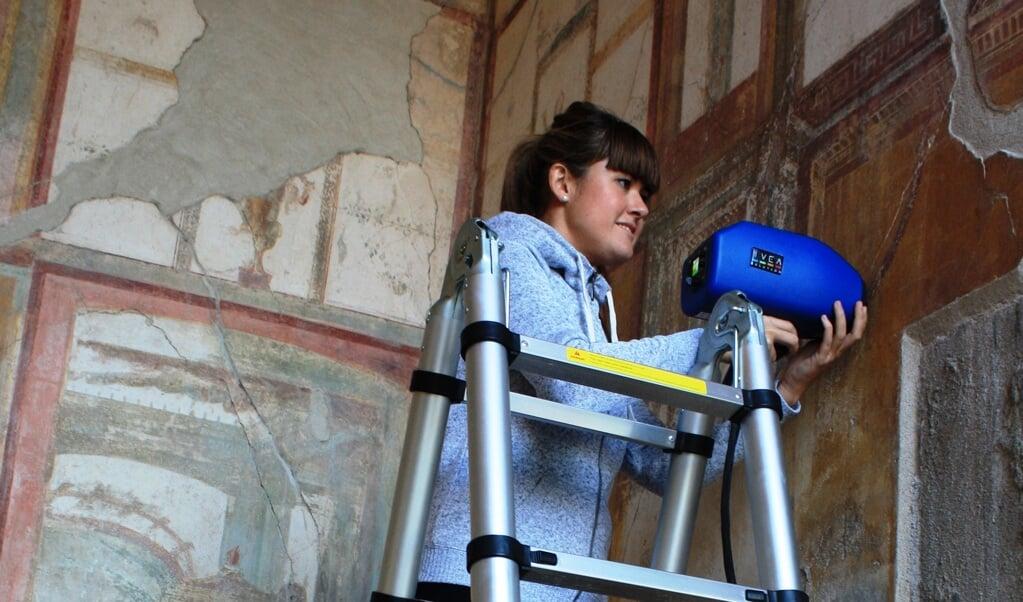 Baskische onderzoeker meet de chemische samenstelling van pigment in een muurschildering in Pompeï.  (beeld Universiteit van Baskenland)