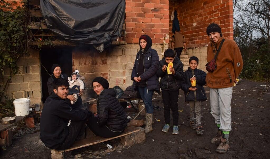 Vahid (rechts) met zijn familie voor het huis in Bosanska Bojna waar ze onderdak gevonden hebben.  (beeld    Marjolein Koster)