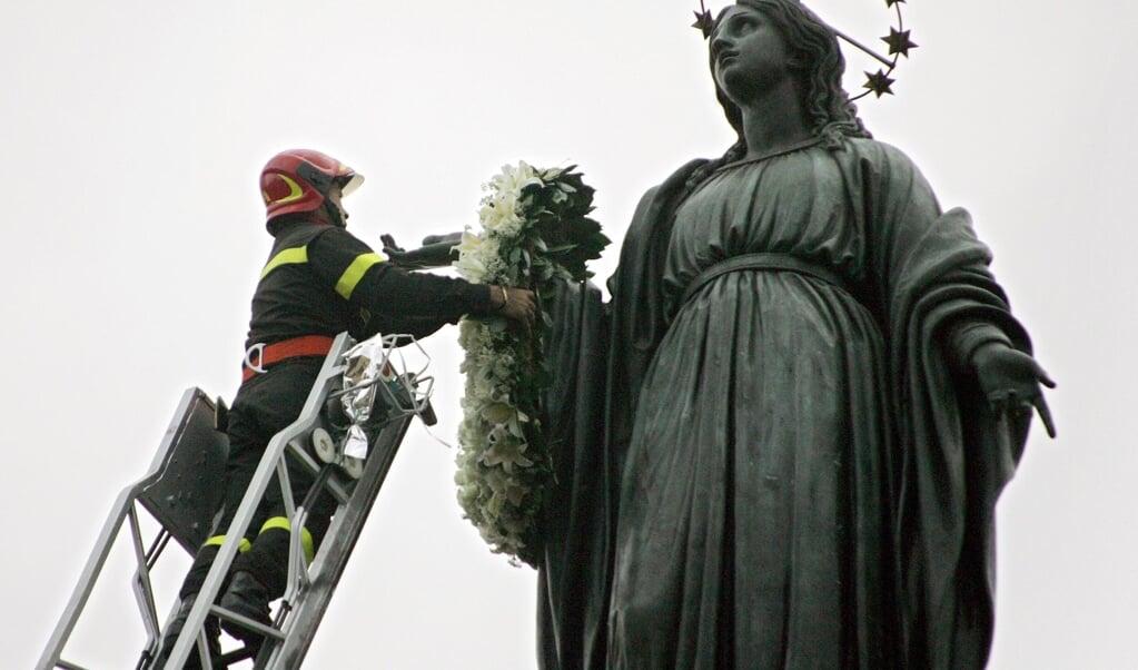 Het Mariabeeld op het Piazza di Spagna krijgt een bloemenkrans, voor de jaarlijkse viering van het dogmafeest op 8 december. Maar die ging dit jaar niet door.  (beeld afp / Andreas Solaro)