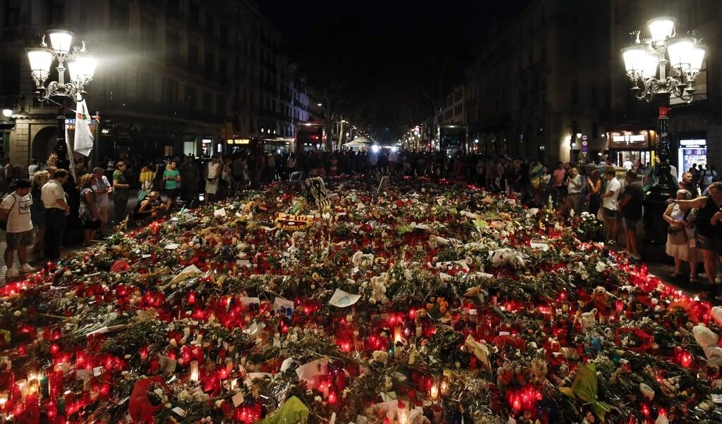 Mensen brengen bloemen, boodschappen en kaarsen om hun medeleven te betuigen met de slachtoffers van de aanslagen in Barcelona en Cambrils, en de nabestaanden. De foto is gemaakt in 2017, kort na de aanslagen.  (beeld afp / Pau Barrena)
