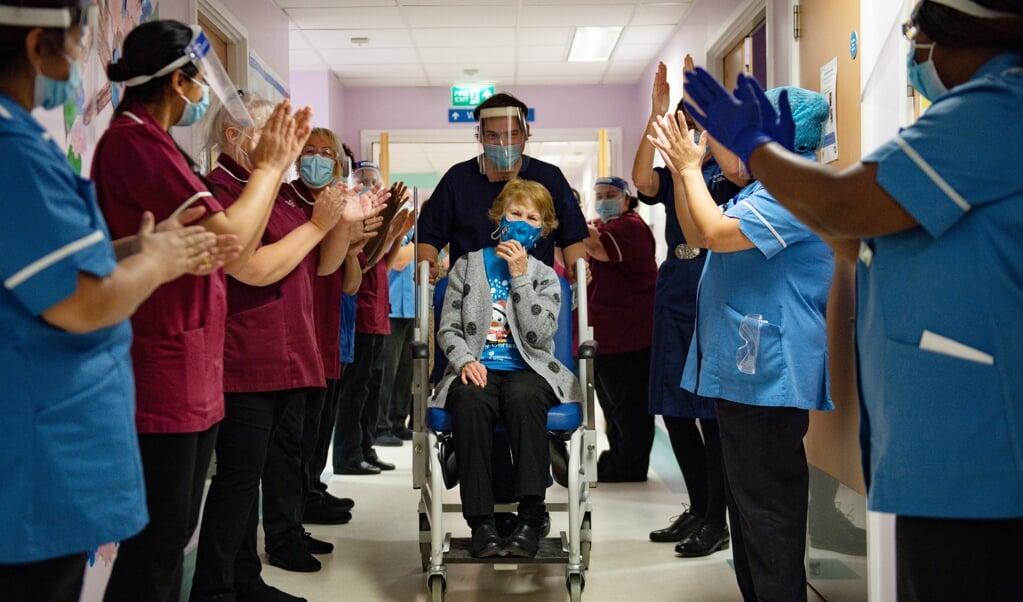 De negentigjarige Margaret Keenan krijgt applaus nadat ze als eerste in Groot-Brittannië het Pfizervaccin had toegediend gekregen in een ziekenhuis in Coventry.  (beeld afp / Jacob King)
