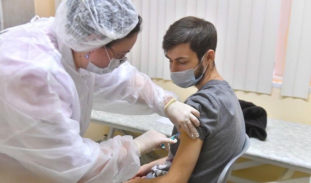 Een zorgmedewerker laat zich als een van de eerste Russen inenten.  (beeld epa / Sergey Kisilev)