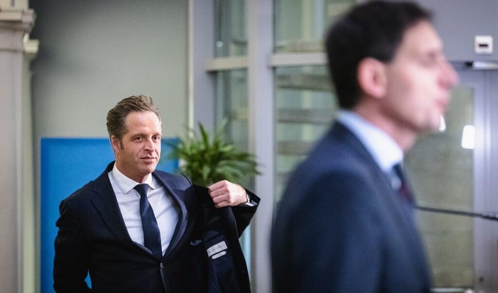 Hugo de Jonge trekt zijn jas aan nadat hij samen met Wopke Hoekstra de pers te woord heeft gestaan.  (beeld anp / Sem van der Wal)