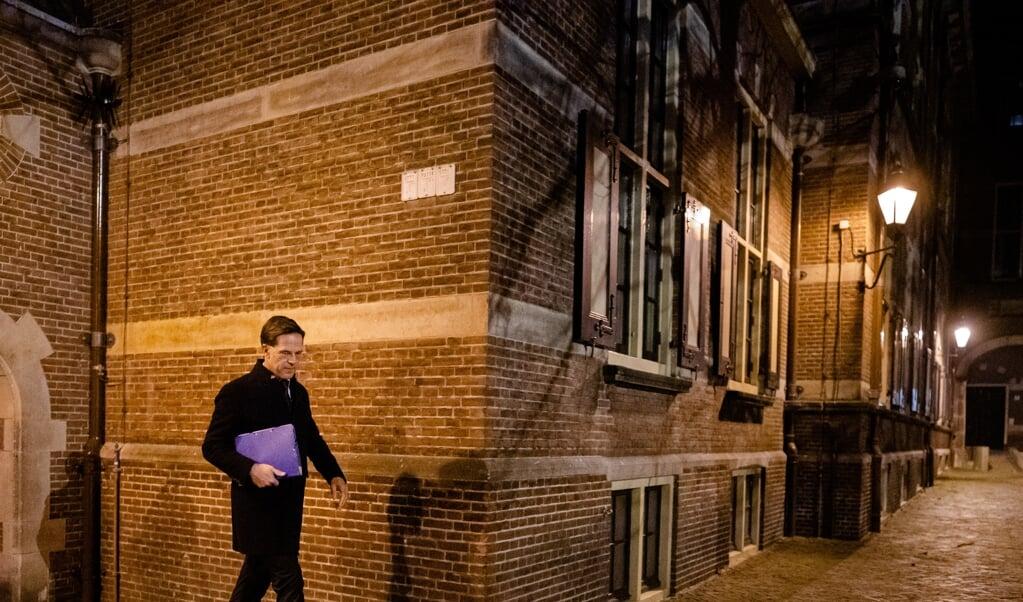 Premier Mark Rutte loopt over een leeg Binnenhof na afloop van het coronadebat.  (beeld anp / Bart Maat)