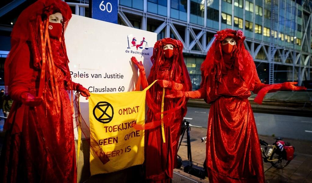 Actievoerders bij de rechtbank waar Milieudefensie samen met zes andere organisaties een zaak heeft aangespannen tegen Shell.   (beeld anp / Robin van Lonkhuijsen)