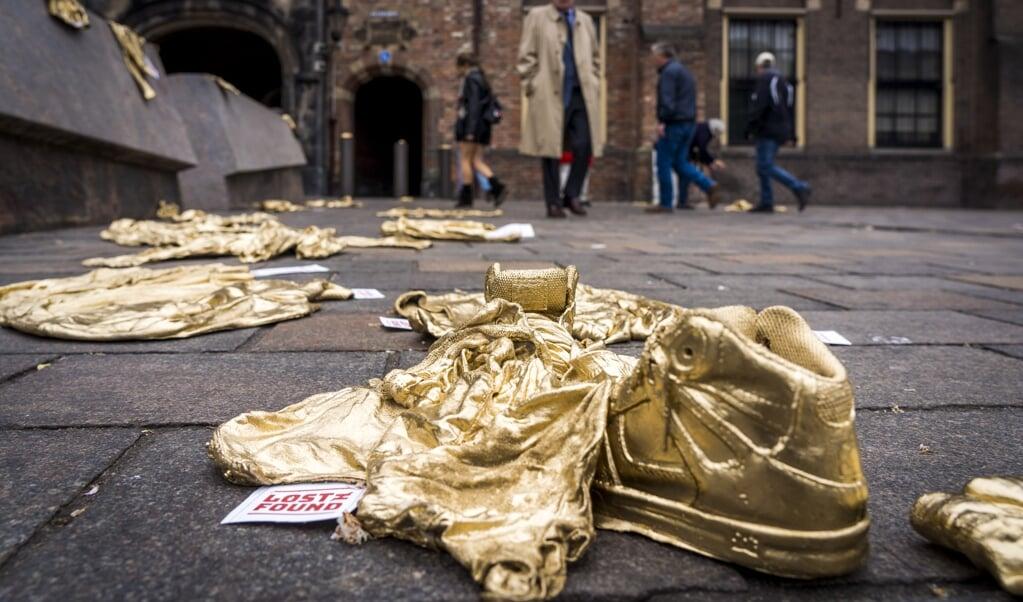 Een kunstzinnige actie voor mensenrechten, mei 2019, Den Haag: gouden kinderkleren vestigen de aandacht op meer dan tienduizend verdwenen vluchtelingenkinderen in Europa. Mensenrechten zijn nauw verbonden met wie God is.  (beeld anp / Lex van Lieshout)