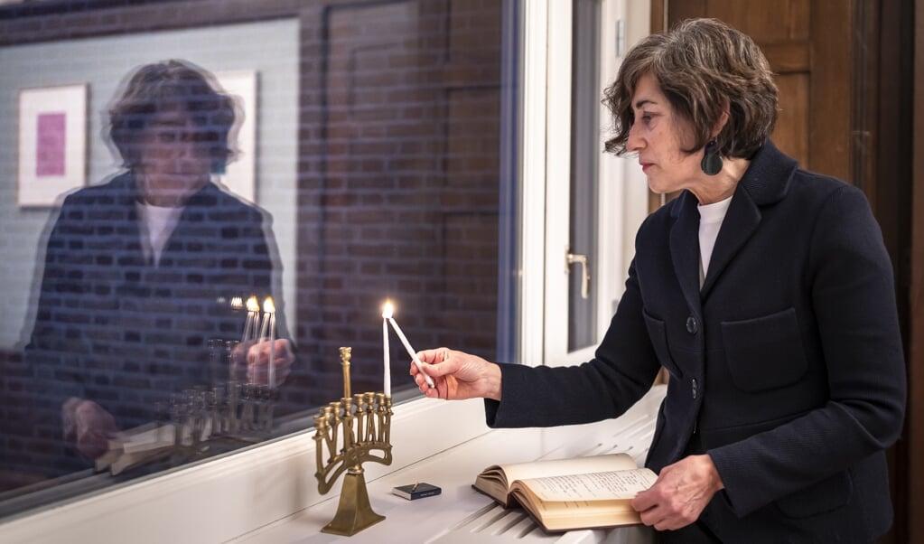 Judith Frishman steekt donderdagavond het eerste van de in totaal 44 kaarsjes voor de Chanoeka-week aan.  (beeld Martin Waalboer)