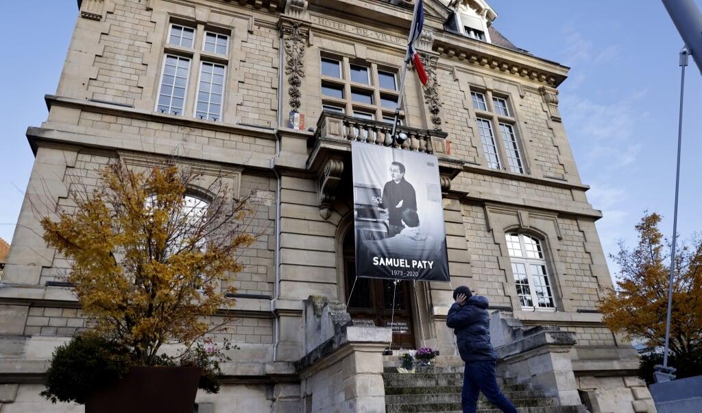 Bij het stadhuis van Conflans-Sainte-Honorine hangt als eerbetoon de beeltenis van Samuel Paty.  (beeld afp / Thomas Coex)