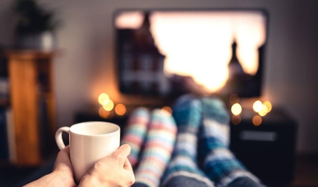 Een goedkope kerstfilm kijken kan een manier zijn om jezelf te troosten.  (beeld istock)