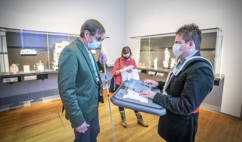 Hannes Wallrafen legt in het Rijksmuseum de werking van zijn prototype kaart uit aan een vrijwilliger.   (beeld Jeroen Jumelet)