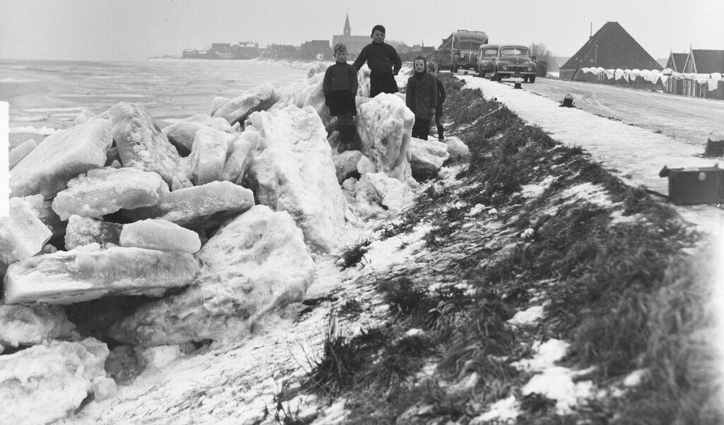 Kinderen spelen bij het kruiende ijs aan de Noordeinde in Volendam.  (beeld Nationaal Archief)