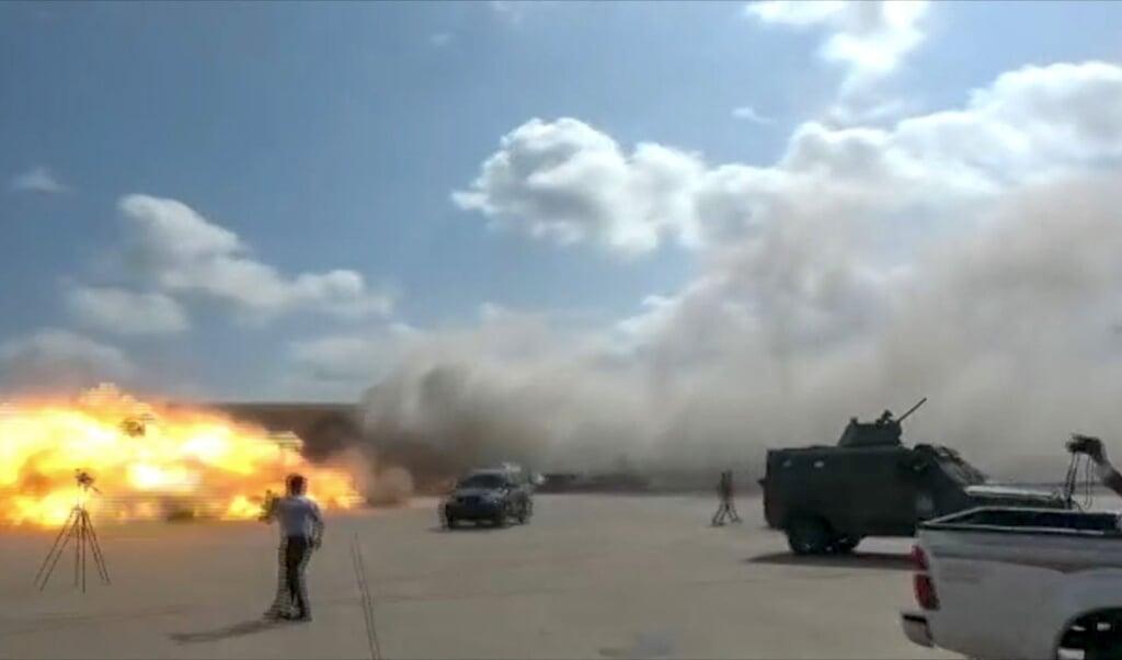 Het moment dat een van de mortiergranaten inslaat op het vliegveld van Aden, terwijl de nieuwe regering van Jemen net uit het vliegtuig stapt.  (beeld  afptv / afp)