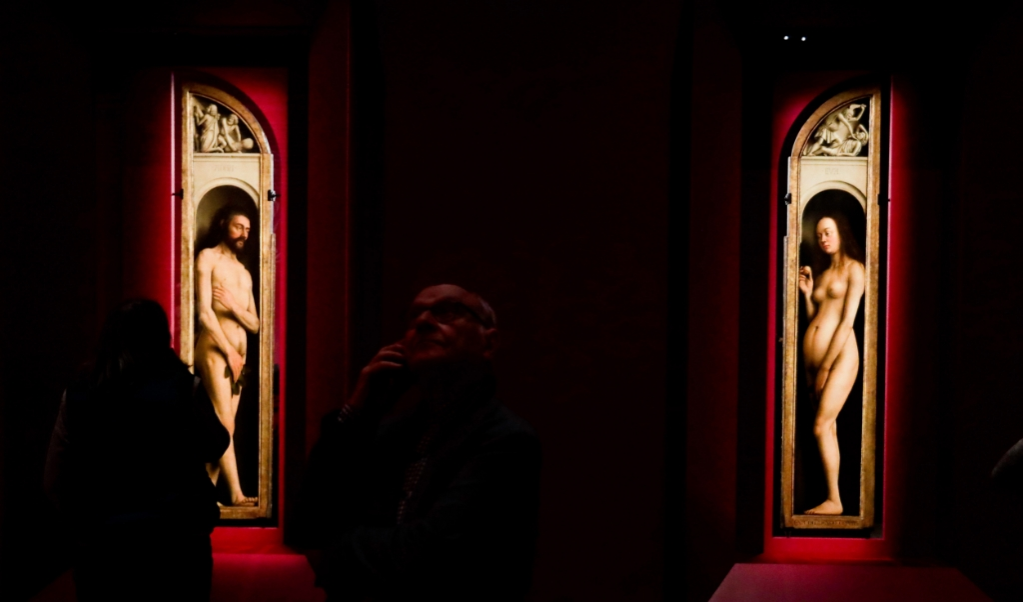 Bezoekers van de tentoonstelling Van Eyck kijken naar de panelen Adam en Eva. Hamvraag: zijn de vijgenblaadjes origineel, of preutse toevoegingen?  (beeld epa / Stephanie Lecocq)