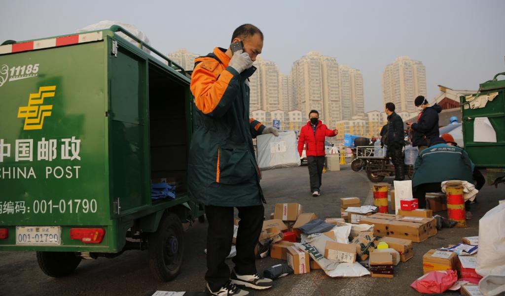 Een koeriersbedrijf levert mondkapjes in Peking, ter bescherming van het nieuwe coronavirus.  (beeld Epa / Wu Hong)