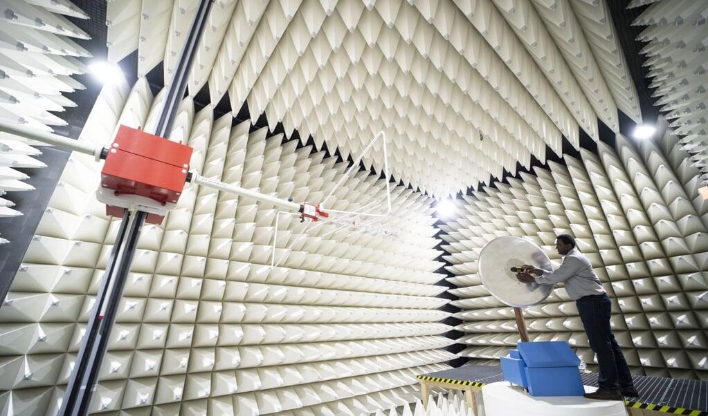 Een medewerker van Continental in Regensburg, Duitsland, toont een G5-antenne is een meetruimte van het bedrijf. Op deze locatie ontwikkelt Continental elektronische systemen voor zelfrijdende vervoersmiddelen, die gebruikmaken van 5G-technologie.   (beeld epa/lukas Barth-tuttas)