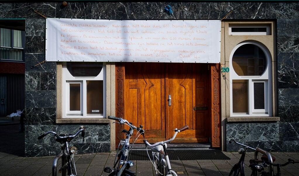 Bij Moskee El Islam in de Haagse Schilderswijk hangt een spandoek dat ze voorlopig dicht zijn. Den Haag ontwaakt een dag nadat het kabinet aangescherpte maatregelen heeft aangekondigd tegen het coronavirus.  (beeld anp / Phil Nijhuis)