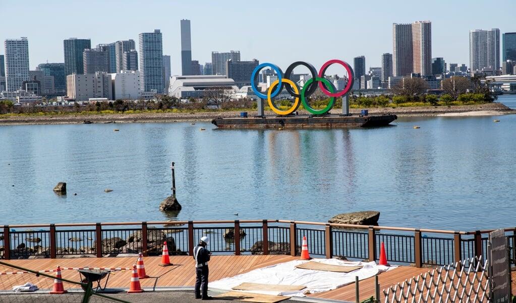 Werkzaamheden nabij de Olympische ringen in Tokio, een dag na de historische beslissing de Spelen met een jaar uit te stellen.  (beeld afp / Behrouz Mehri)