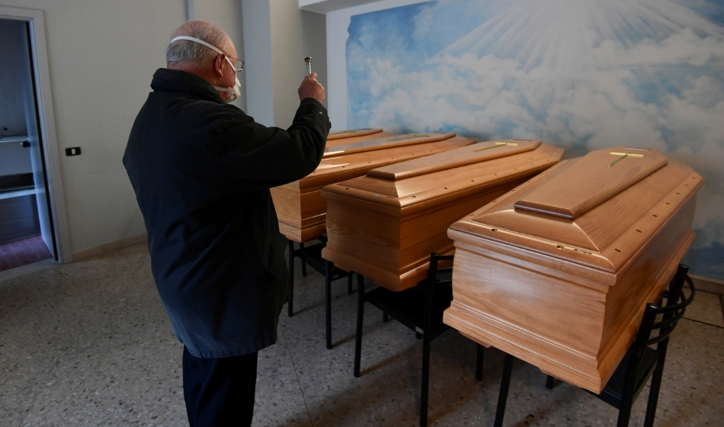 Een Italiaanse priester in het stadje Albino zegent de kisten van aan het coronvirus overleden parochianen.  (beeld afp / Miguel Medina)
