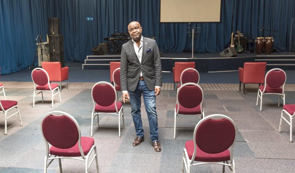Pastor Nana Baiden in zijn kerk. Nu collecte-inkomsten door de coronacrisis uitblijven, kan de hypotheek niet meer betaald worden.  (beeld Martin Waalboer)
