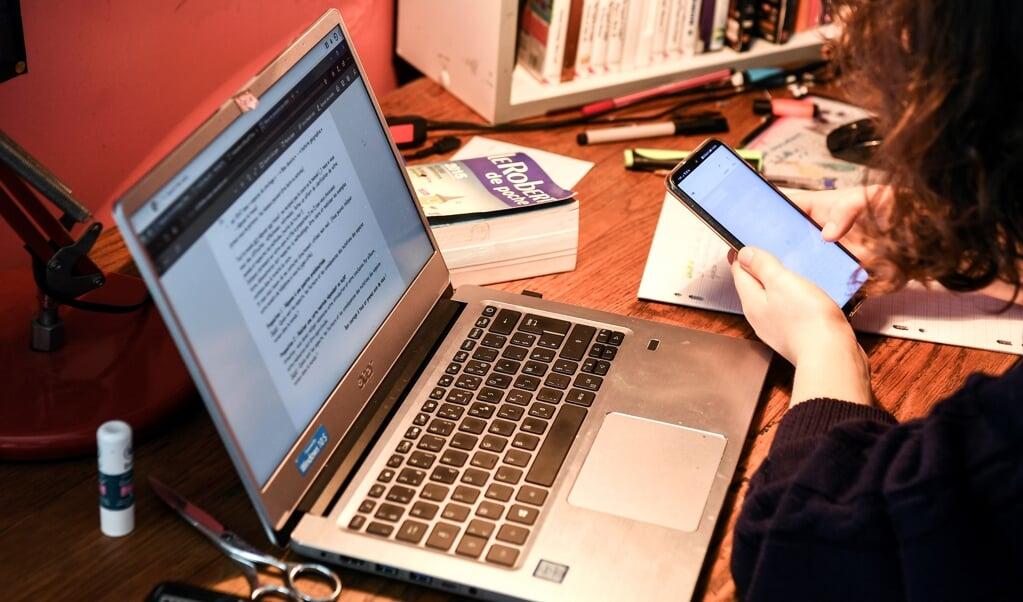 Je zit als student achter je laptop. Dit werkt vervreemdend.  (beeld afp / Alain Jocard)