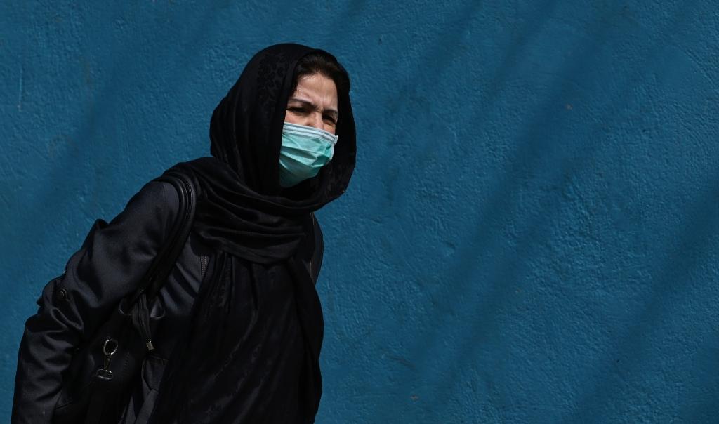 Een vrouw draagt een mondmasker in de Afghaanse hoofdstad Kabul op 29 maart 2020.  (beeld afp / Wakil Kohsar)