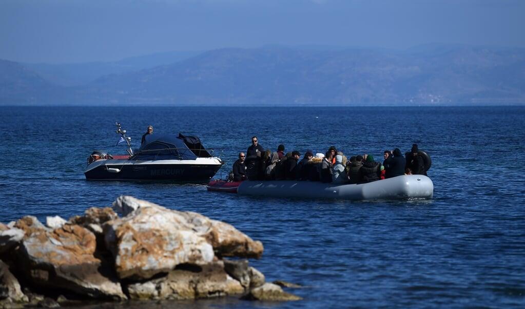 Vluchtelingen in boten stuiten vanaf eind augustus op een drijvende barrière van drie kilometer lang.   (beeld afp / Aris Messinis)