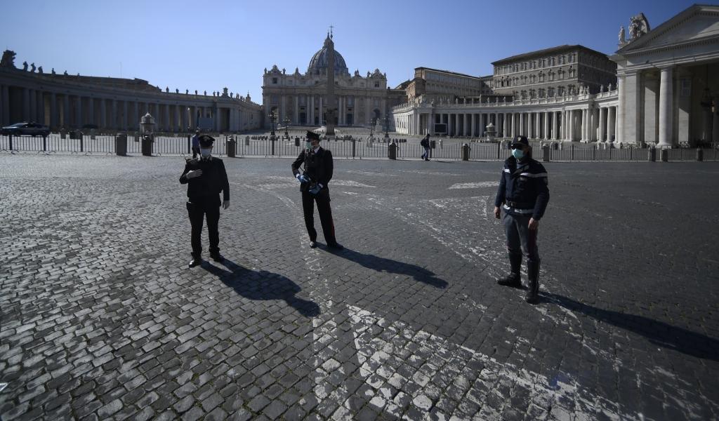 Italiaanse politiemensen bij een verlaten Sint-Pietersplein.  (beeld Filippo Monteforte / AFP)