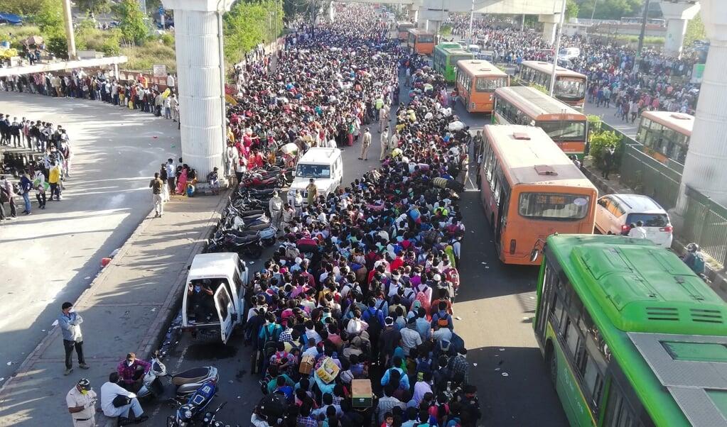 Duizenden arbeidsmigranten verdrongen zich zaterdag in Delhi, in de hoop toch een bus de stad uit te kunnen nemen.  (beeld Bhuvan Bagga / AFP)