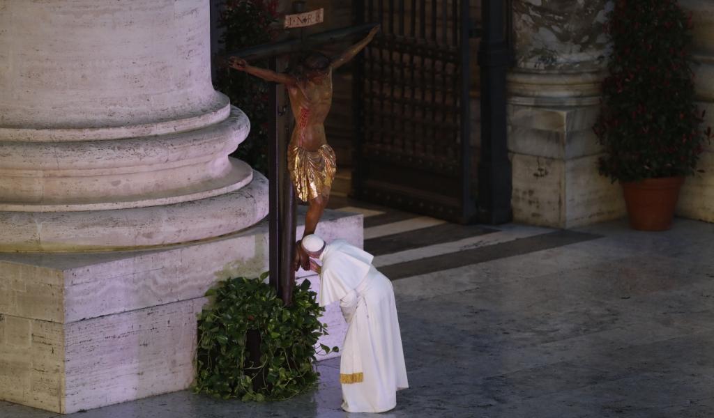 Paus Franciscus groet het kruis dat voor de Sint-Pieter is geplaatst, voorafgaand aan de uitzonderlijke urbi-et-orbizegen op vrijdag 27 maart 2020.  (beeld afp / Yara Nardi)