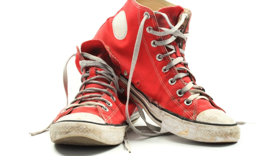 Old and dirty red canvas sneakers, isolated over white  (beeld istock)