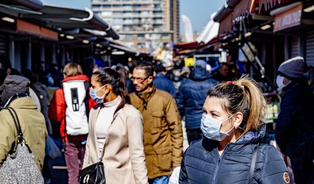 Bezoekers aan de Haagse markt lopen met mondkapjes op. Ondanks de coronaregels is het er erg druk.  (beeld anp / Robin Utrecht)
